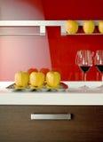 Appelen en wijnglazen op de vloer van een moderne keuken Stock Fotografie