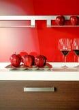 Appelen en wijnglazen op de vloer van een moderne keuken Stock Afbeeldingen
