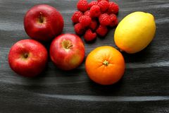 Appelen, groep frambozen, citroen en bloedsinaasappel op zwarte raad Stock Foto