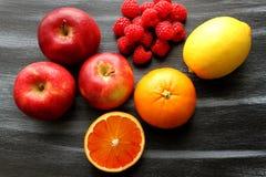 Appelen, groep frambozen, citroen en bloedsinaasappel op zwarte raad Royalty-vrije Stock Foto