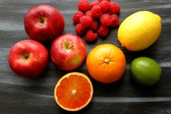 Appelen, groep frambozen, citroen, kalk en bloedsinaasappel op zwarte raad Stock Foto's