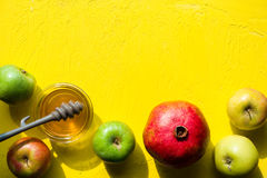 Appelen met honing, granaatappel op een gele lijst voor het Joodse Nieuwjaar Stock Afbeeldingen