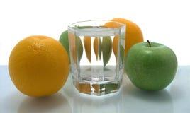 Appelen met sinaasappelen en glas water royalty-vrije stock fotografie