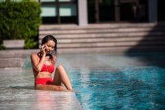 Appeler tous ses amis pour se joindre Portrait d'une jeune femme heureuse s'asseyant par la piscine parlant sur son rire de télép Image libre de droits