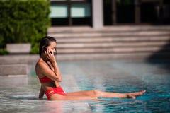 Appeler tous ses amis pour se joindre Portrait d'une jeune femme heureuse s'asseyant par la piscine parlant sur son rire de télép Photo libre de droits