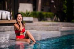 Appeler tous ses amis pour se joindre Portrait d'une jeune femme heureuse s'asseyant par la piscine parlant sur son rire de télép Photographie stock libre de droits