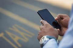 Appeler un taxi avec le smartphone photo stock