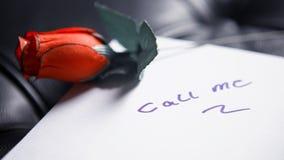 Appelez-moi écrit sur le papier avec la rose de rouge Image stock