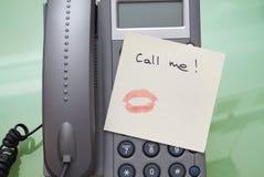 Appelez-moi écrit sur un billet avec le baiser avec le rouge à lèvres sur le phone Images libres de droits