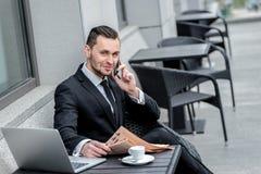 Appelez un ami Jeune homme d'affaires jugeant un téléphone et une lecture nouveaux Photo stock