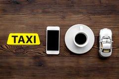 Appelez un taxi avec l'APP mobile et la tasse de copyspace en bois de vue supérieure de fond de table de café Photos stock