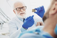 Appellieren des männlichen Zahnarztes, der Erklärung gibt stockbild