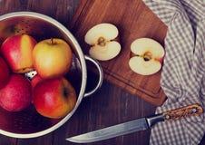 Appels σε έναν διηθητήρα, ένα μαχαίρι και μια πετσέτα στον ξύλινο πίνακα Στοκ φωτογραφίες με δικαίωμα ελεύθερης χρήσης