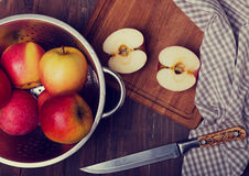 Appels in a strainer, knife and napkin on the wooden table Royalty Free Stock Photos