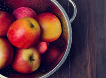 Appels in a strainer on the wooden table,  toned photo Stock Photos