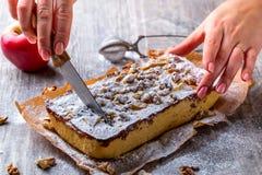 Appeltaart, met gepoederde suiker en Hand wordt de bestrooid snijdt de cake die Re Stock Foto