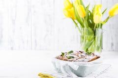 Appeltaart in schotels op een witte achtergrond en een boeket van de lente gele tulpen Eigengemaakte gebakjes met fruit voor heer royalty-vrije stock afbeelding