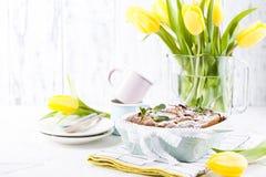 Appeltaart in schotels op een witte achtergrond en een boeket van de lente gele tulpen Eigengemaakte gebakjes met fruit voor heer stock afbeelding