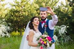 Appena coppia sposata che fa selfie in parco fotografia stock