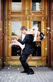 Appena coppia sposata inondata in petali di rosa Immagine Stock