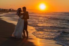 Appena giovani coppie sposate su una spiaggia nebbiosa al crepuscolo Fotografia Stock Libera da Diritti