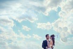 Appena sposa e sposo sposati con i baloons a disposizione sopra la SK nuvolosa Fotografia Stock
