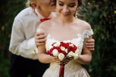 Appena uomo sposato che bacia sposa nel parco verde immagine stock