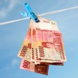 Appendendo sulla rupia indonesiana delle banconote della corda Fotografie Stock