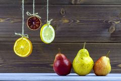 Appendendo sulle fette delle corde di limone, di arancia e di limetta Sulla tavola posto pere dolci mature Fotografia Stock