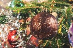 Appendendo sulle palle di Natale del ramo sui precedenti del lamé di Natale Fotografie Stock Libere da Diritti