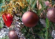 Appendendo sulle palle di Natale del ramo sui precedenti del lamé di Natale Fotografia Stock Libera da Diritti