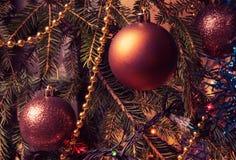 Appendendo sulle palle di Natale del ramo sui precedenti del lamé di Natale Immagini Stock Libere da Diritti