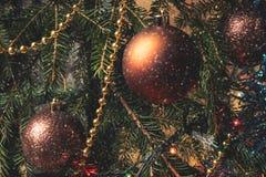 Appendendo sulle palle di Natale del ramo sui precedenti del lamé di Natale Fotografia Stock