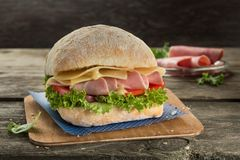 Appetising ciabatta sandvich with ham, cheese, tomato and green salad on the wooden background. Appetising ciabatta sandvich with ham, tomato and green salad stock image