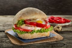 Appetising ciabatta sandvich with ham, egg , tomato, sweet red pepper and green salad on the wooden background. Appetising ciabatta sandvich with ham, tomato and stock images