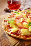 Appetising ham and pineapple Italian pizza. Closeup view of an appetising ham and pineapple Italian pizza with a crisp golden crust served on an old grunge stock image