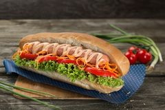 Appetising hot dog with vegetables and green salad close up on a wooden background. Appetising hot dog with vegetables close up on a wooden background stock image