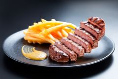 Appetising steak slices levitate above the black plate. Creative shot of steak and french fries on a dark background. Appetising steak slices levitate above the royalty free stock photography