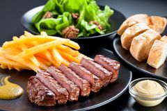Appetising steak slices served with fries , green salad and baguette on a black plate. Appetising steak slices served with fries and green salad the black plate royalty free stock images