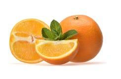 Appetitanregende Zusammensetzung von geschnittenen saftigen Orangen und Zweige der grünen Pfefferminz stockbilder