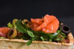 Appetitanregender Aperitif von Canape, roter Fisch, Salat in einem Restaurant auf einem Betonhintergrund des dunklen Schwarzen St lizenzfreie stockfotografie
