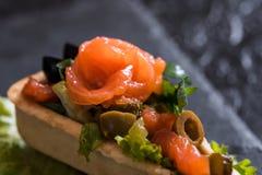 Appetitanregender Aperitif von Canape, roter Fisch, Salat in einem Restaurant auf einem Betonhintergrund des dunklen Schwarzen St stockbild