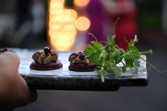 Appetitanregender Imbiss - Kastanienpastete mit Grüns auf einer dunklen Platte lizenzfreie stockfotos
