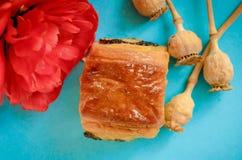 Appetitanregendes Brötchen mit der Mohnblume verziert mit einer cyan-blauen Blume auf einem Blau lizenzfreie stockfotos