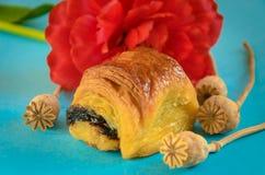 Appetitanregendes Brötchen mit der Mohnblume verziert mit einer cyan-blauen Blume auf einem Blau lizenzfreie stockbilder