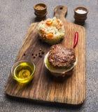 Appetitanregendes Fleisch des Burgers nur und Eier und Butter, mit Reis und Gemüse, Gewürze auf Weinleseschneidebrett lizenzfreie stockbilder