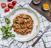 Appetitanregendes Lammgemüse auf einer weißen Platte mit Tomate und Petersilie würzte und Gabel auf einem karierten Draufsichtabs Lizenzfreies Stockbild