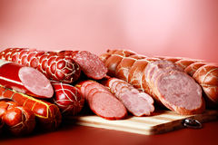 Appetite meat. Tasty sausages on the red background stock images