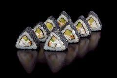 Appetitsatz Sushirollen mit Avocado, Aal und Gurke im schwarzen indischen Sesam auf einer schwarzen Hintergrundnahaufnahme Stockbild