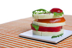 Appetizer. A light snack of cheese, tomato, and rocket salad Royalty Free Stock Photos